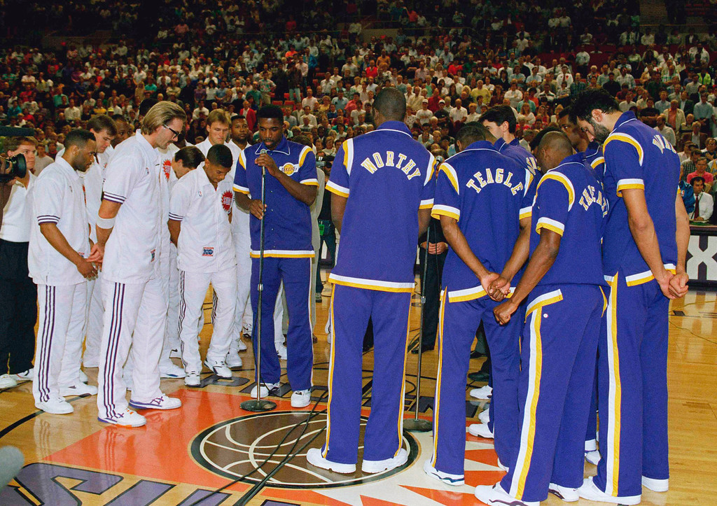 . Los Angeles Lakers A.C. Green leads teammates and Phoenix Suns in a prayer for retired Lakers guard Magic Johnson, who announced his retirement after testing positive for the HIV virus, Nov. 9, 1991.  (AP Photo/Jeff Robbins)