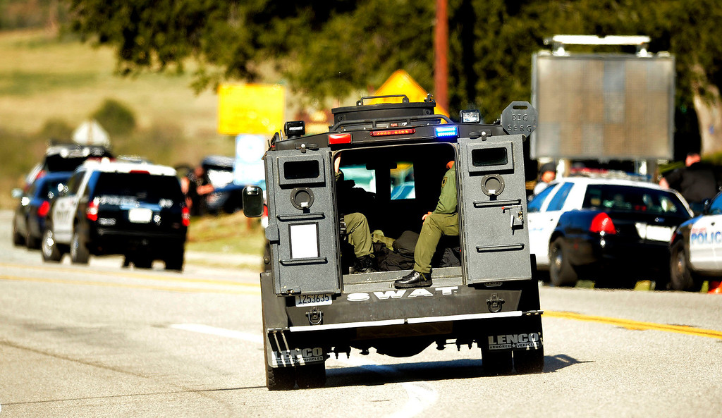 Description of . A SWAT team enters a blockade at Highway 38 and Bryant Street near the Mill Street Ranger Station west of Yucaipa February 12, 2013.   Authorities believe that they exchanged gunfire with fugitive Christopher Dorner in the Angles Oaks area of the San Bernardino National Forest.  Fish and Game officers spotted a man fitting the description of Dorner driving a white pick-up, and two San Bernardino County Sheriff Deputies exchanged gunfire with him.  Authorities believe Dorner is holed up in a cabin on Glass Road and Highway 38.  GABRIEL LUIS ACOSTA/STAFF PHOTOGRAPHER.