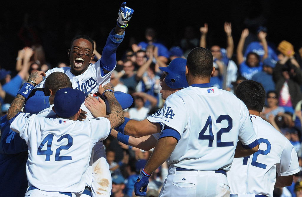 . Los Angeles Dodgers\' Dee Gordon jumps into the arms of Matt Kemp as teammates mob him after hitting a game winning single with bases loaded as Juan Rivera scores to beat the San Diego Padres 5-4 in the ninth inning of a baseball game in Los Angeles on Sunday, April 15, 2012.   (Keith Birmingham/Pasadena Star-News)