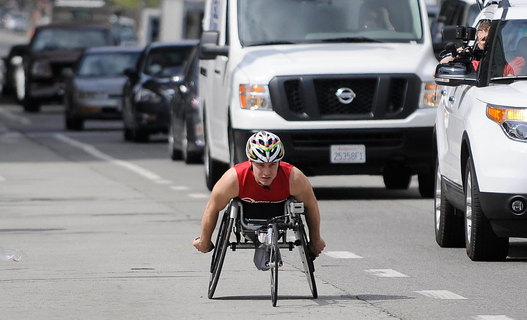 ". Ryan Chalmers wheels down Main Street in Los Angeles. Chalmers is pushing himself in a wheel chair on a coast-to-coast trip that starts at the JW Marriott in Los Angeles, and will end in New York\'s Central Park. The 3000 mile odysey will raise funds for an organization called  ""Stay Focused\"" that allows teens and young adults with disabilities to participate in sports alongsid able-bodied people.  Los Angeles CA 4/6/2013(John McCoy/Staff Photographer"