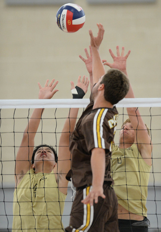 . Bishop Montgomery\'s Ryan Garcia (4) and Eddie Specht (1) look to block Parker\'s David Nussbaum (13) in a Southern California Regional Division III Final volleyball match Saturday at Santiago Canyon College in Orange. The match came down to the final points of the fifth game, with Bishop Montgomery losing the heart-breaker. Bishop Montgomery vs. Francis Parker (San Diego) 20130525 Photo by Steve McCrank / Staff Photographer