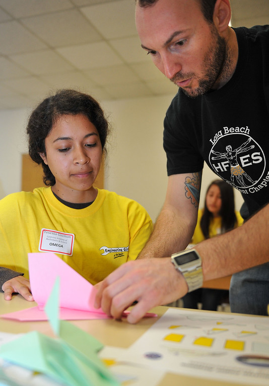 . 3/15/13 - Zach Roberts, a first year grad student in Human Factors Engineering Science, helps Yesenia Guzman with a paper space shuttle. The girls were on campus for the Cal State Long Beach�s (CSULB) annual �Engineering Girls at the Beach.�  The event hosts some 250 high school, middle school and elementary school girls and boys for an understanding of engineering, computer science, technology and other non-traditional career fields. Photo by Brittany Murray / Staff Photographer
