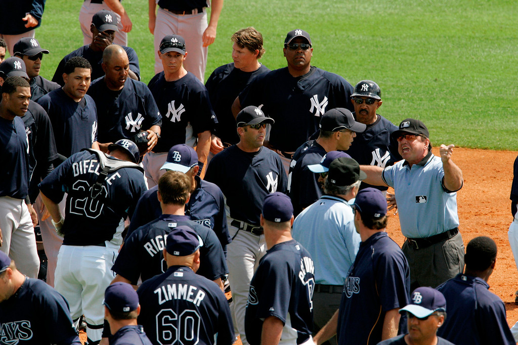 . New York Yankees manager Joe Girardi, left, and coach Tony Pena, top center, talk with umpire Charlie Reliford as a second inning brawl with the Tampa Bay Rays sorts itself out in spring baseball action in St. Petersburg, Fla.,  Wednesday, March 12, 2008.(AP Photo/Gene J. Puskar)