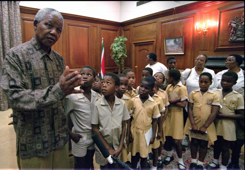 . President Nelson Mandela, left, talks with a group of touring school children in his office in Pretoria Thursday September 28, 1995. Mandela had spotted the children visiting the Government\'s Union Buildings, where the Presidential offices are situated, and invited the delighted children in for a visit. (AP Photo/Adil Bradlow)