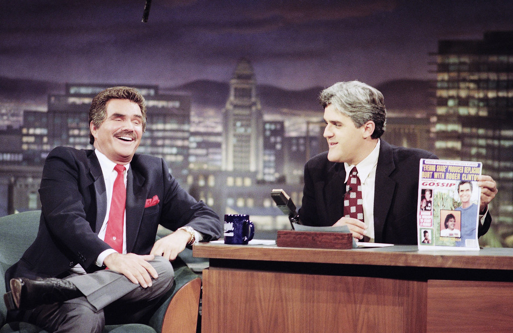 . Actor Burt Reynolds, left, laughs as Jay Leno holds up one of the tabloids featuring the breaking of Reynolds and his wife, Loni Anderson, during the taping of ?The Tonight Show with Jay Leno? in Burbank, California on Monday, Sept. 13, 1993. (AP Photo/Wendy Perl)
