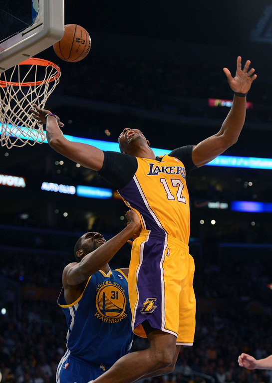 . The Lakers\' Dwight Howard #12 scores as the Warriors\' Festus Ezeli #31 during their game at the Staples Center in Los Angeles Friday, April 12, 2013. (Hans Gutknecht/Staff Photographer)