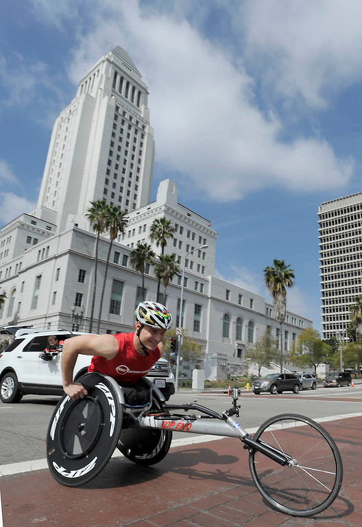 ". Ryan Chalmers wheels past Los Angeles City Hall. Chalmers is pushing himself in a wheel chair on a coast-to-coast trip that starts at the JW Marriott in Los Angeles, and will end in New York\'s Central Park. The 3000 mile odysey will raise funds for an organization called  ""Stay Focused\"" that allows teens and young adults with disabilities to participate in sports alongsid able-bodied people.  Los Angeles CA 4/6/2013(John McCoy/Staff Photographer"