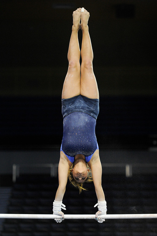 . UCLA\'s Monique De La Torre practices on the uneven bars. (Michael Owen Baker/Staff Photographer)