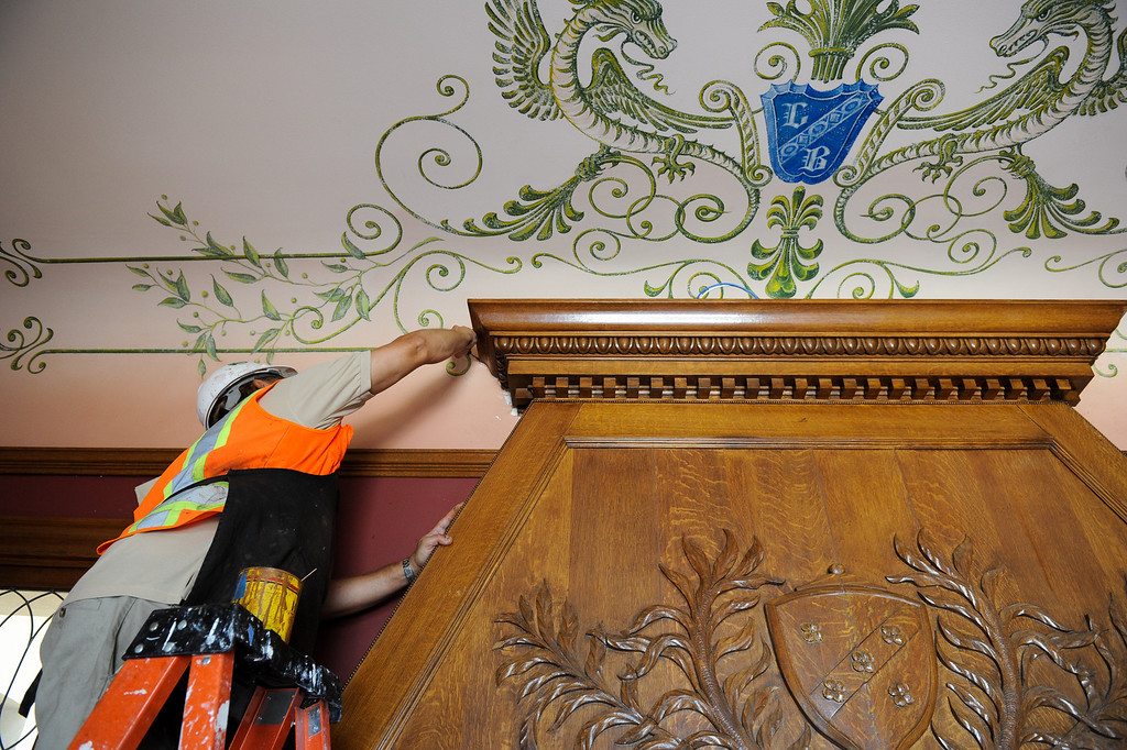 . Pablo Juarez touches up paint at a fireplace mantel in Glendale�s historic Brand Library & Art Center during its 18-month renovation. Tuesday, July 23, 2013. (Michael Owen Baker/L.A. Daily News)
