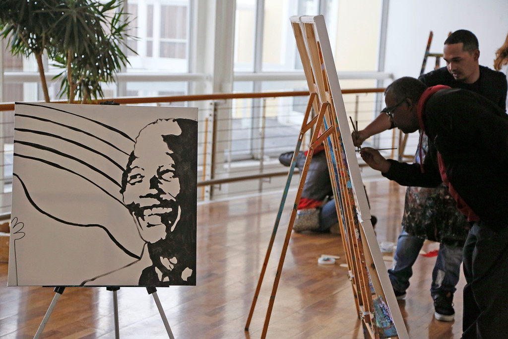 . The face of former South African President Nelson Mandela is displayed as people paint during his birthday celebrations in Cape Town, South Africa, Friday, July 18, 2014.  (AP Photo/Schalk van Zuydam)