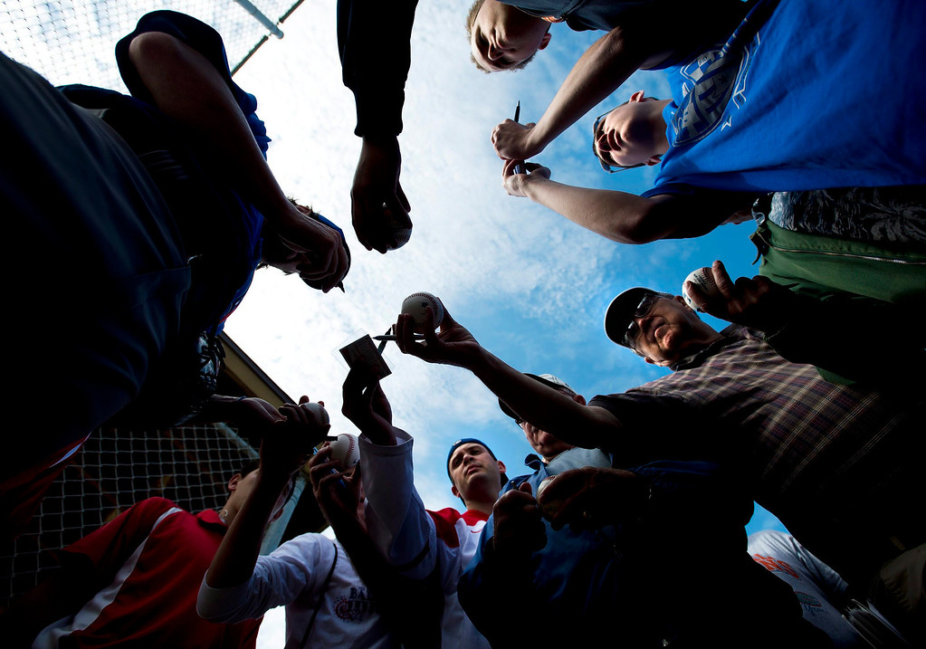. Toronto Blue Jays starting pitcher R.A. Dickey, left, signs autographs for fans during baseball spring training in Dunedin, Fla., on Tuesday, Feb. 19, 2013. (AP Photo/The Canadian Press, Nathan Denette)