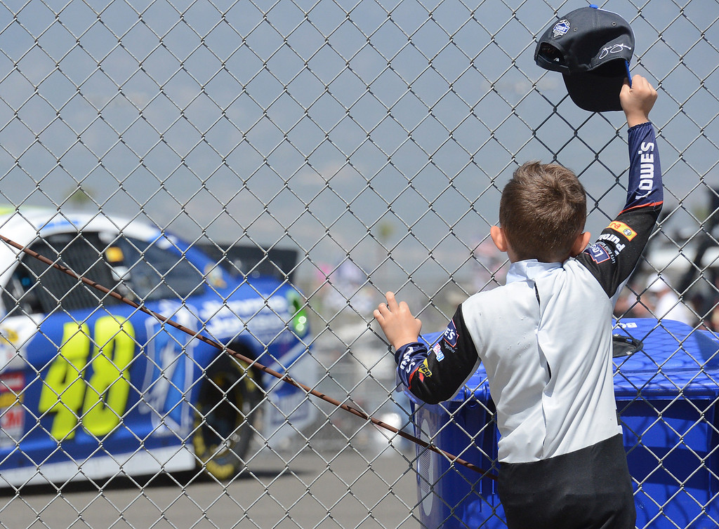 . (Will Lester/Staff Photographer) NASCAR fan Easton Shortle, 5 from Seal Beach, wears the uniform of his favorite driver Jimmie Johnson as he waves to Johnson as he drives by Friday March 22, 2013 at Auto Club Speedway in Fontana.