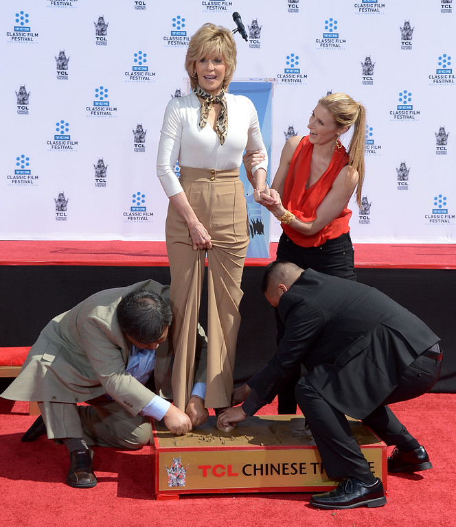 . Actress Jane Fonda prints her feet in wet cement during her Handprint/Footprint Ceremony during the 2013 TCM Classic Film Festival at TCL Chinese Theatre on April 27, 2013 in Los Angeles. Fonda is an American actress, writer, political activist, former fashion model, and fitness guru. She rose to fame in the 1960s with films such as Barbarella and Cat Ballou. She has won two Academy Awards, an Emmy Award, three Golden Globes and received several other movie awards and nominations during more than 50 years as an actress. After 15 years of retirement, she returned to film in 2005 with Monster-in-Law, followed by Georgia Rule two years later. She also produced and starred in over 20 exercise videos released between 1982 and 1995, and once again in 2010.  (JOE KLAMAR/AFP/Getty Images)