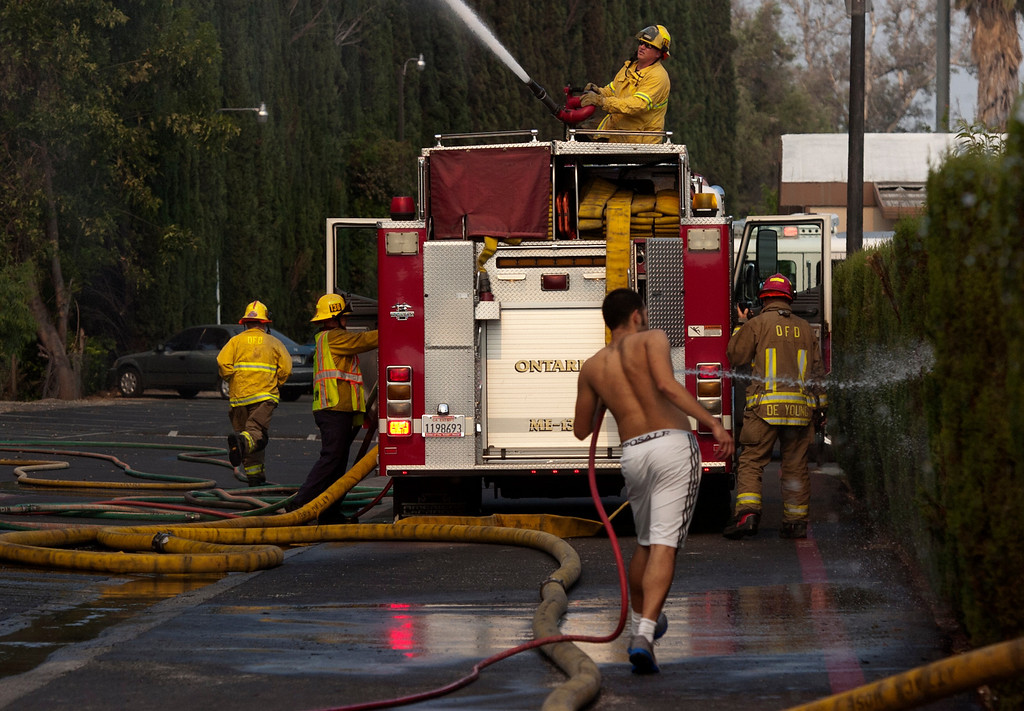 . Ontario firefighters battle a Cypress tree fire as a resident waters down trees near mobile homes at Samoa Village Mobile Home Estates in Ontario, CA, Tuesday, June 10, 2014. (Photo by Jennifer Cappuccio Maher/Inland Valley Daily Bulletin)