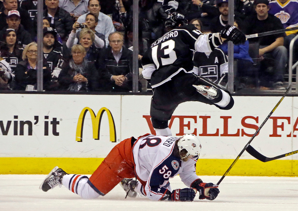 . Los Angeles Kings left wing Kyle Clifford (13) flies over Columbus Blue Jackets defenseman David Savard (58) in the first period of an NHL hockey game in Los Angeles, Thursday, April 18, 2013. (AP Photo/Reed Saxon)
