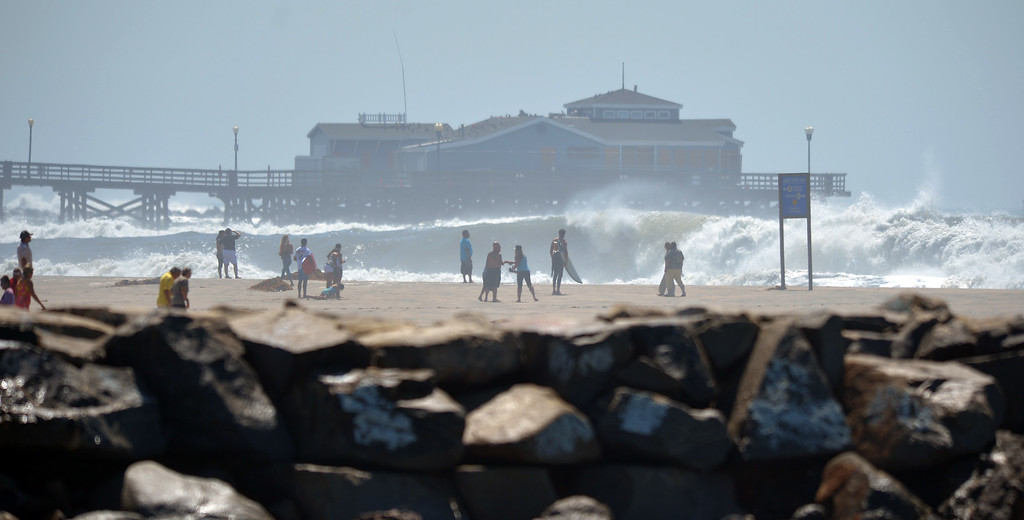 Description of . People line the beach to watch the high waves pound the shore and pier in Seal Beach, CA on Wednesday, August 27, 2014. (Photo by Scott Varley, Daily Breeze)
