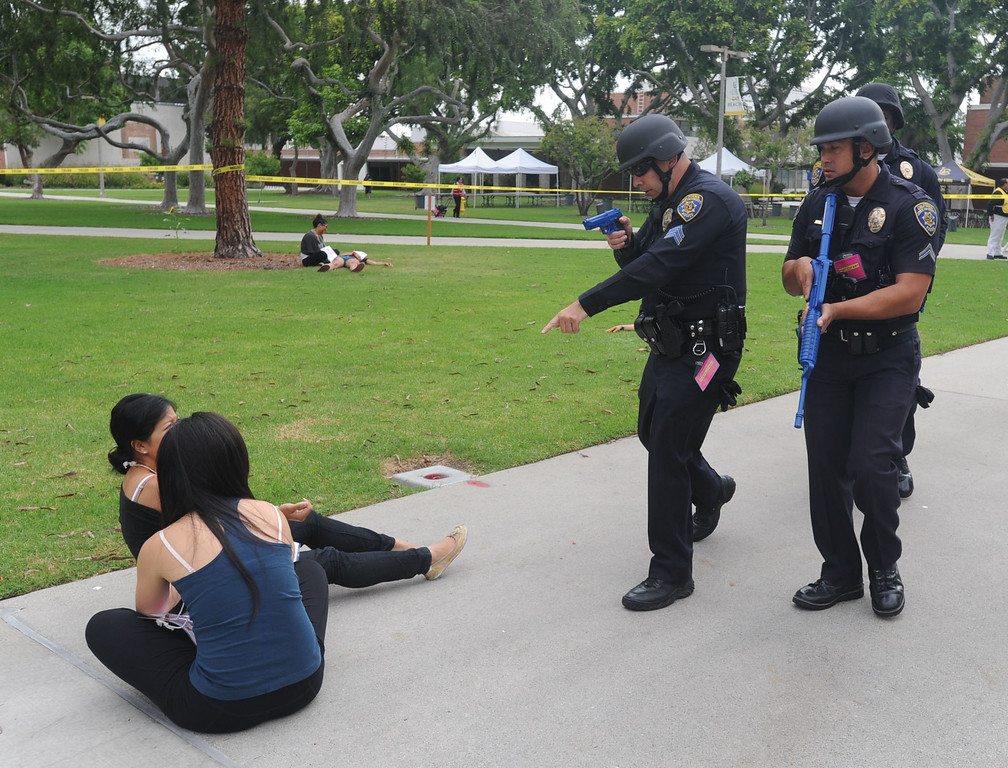 . A multi-agency response exercise to an active shooter and mass casualty incident was held Tuesday on the Cal State Long Beach campus. Fist responding campus police officers move across the campus looking for shooter with fake weapons drawn. 20130813 Photo by Steve McCrank / Staff Photographer