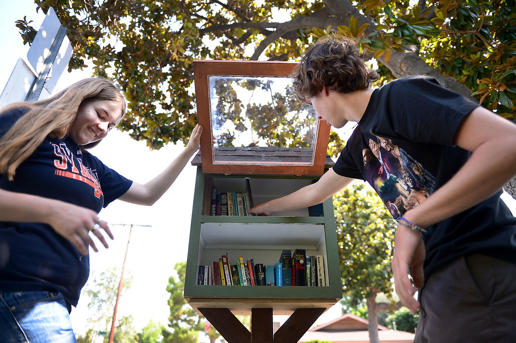 . Stephanie Cox, 18, who created five free neighborhood book nooks in Monrovia for her Girl Scout Gold Award Project, fills the Monrovia Fire Department\'s library box on East Fig Street with books Friday, July 19, 2013 with her friend Travis Stone, 18. (SGVN/Staff Photo by Sarah Reingewirtz)