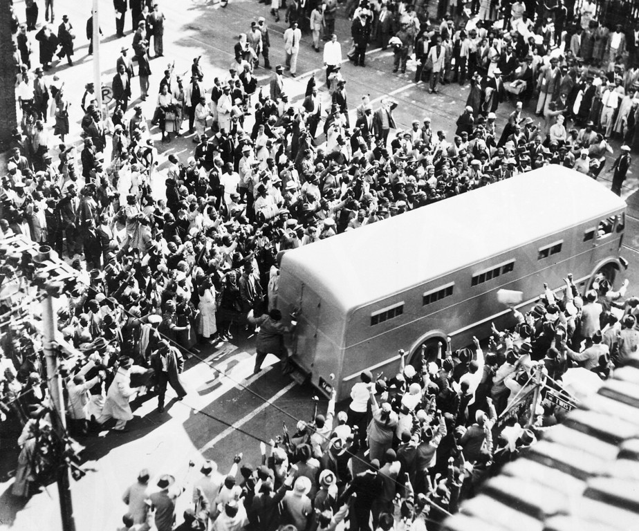 . Crowds cheer as a police van brings prisoners to the Drill Hall, in Johannesburg, South Africa, Dec. 31, 1956, for the start of the \'Treason Trial\'. One man has climbed onto the step of the van top shout encouragement to the inmates. Nelson Mandela was among the people arrested and standing trial. (AP Photo)