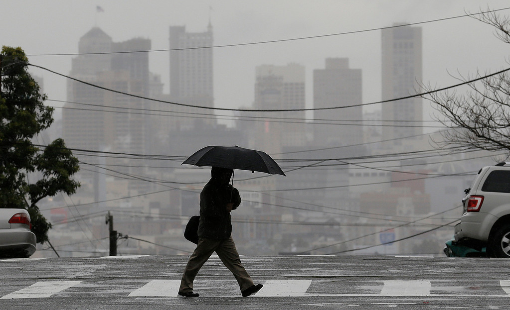 . A man carries an umbrella as he crosses Vermont Street with the San Francisco skyline in the background in San Francisco, Tuesday, Feb. 19, 2013. (AP Photo/Jeff Chiu)