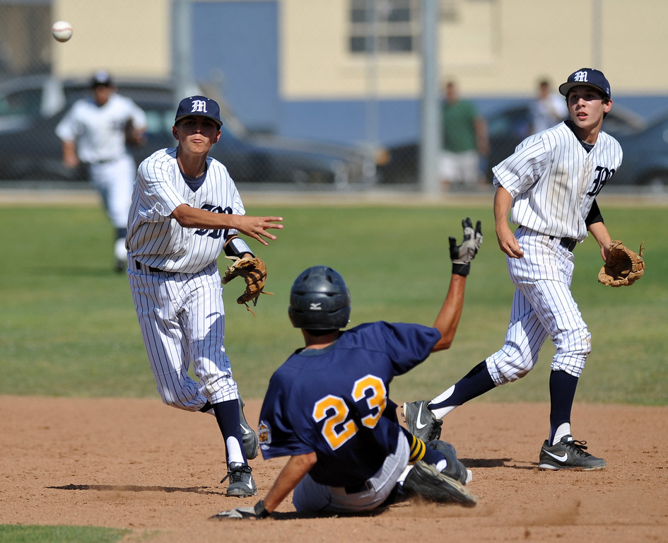 Description of . Montebello second baseman Richard Santoscoy (#5) forces out Alhambra's Alan Rivera (#23) as he throws to complete the double play in their Almont League baseball game at Montebello High School in Montebello  on Friday April 19, 2013. (SGVN/Staff Photo by Keith Durflinger)