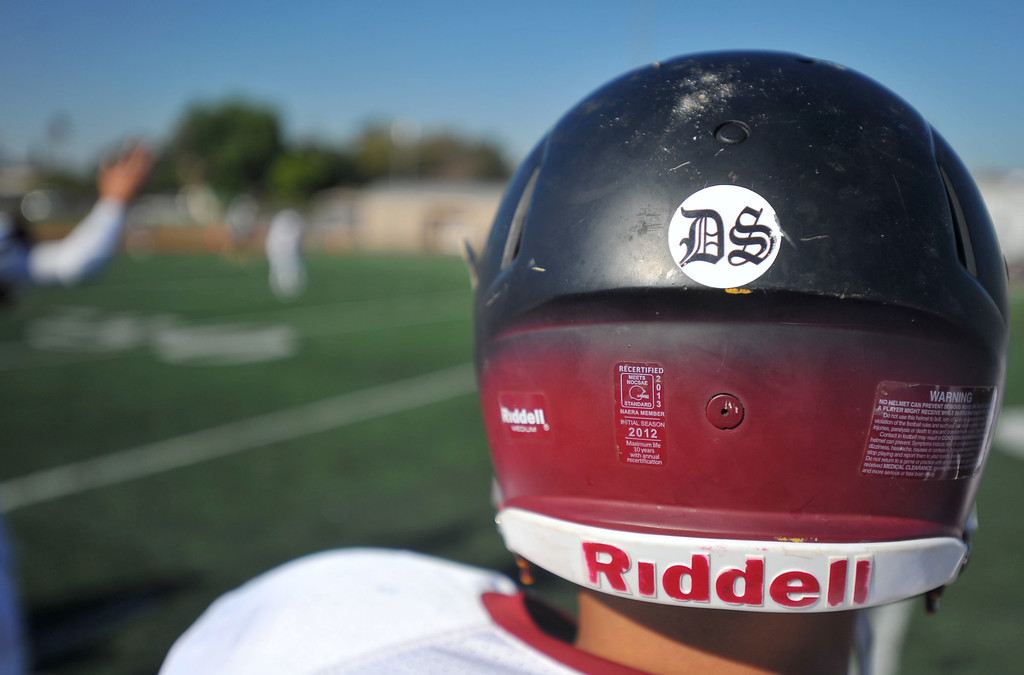 . Teammates of Downey High junior varsity football player Dodi Soza wear stickers of his number 23 on their helmets during their game against Warren in Downey, CA on Thursday, October 17, 2013. Dodi Soza collapsed on the field after scoring a touchdown and died two days later on Saturday. On the first offensive play of Thursdays game, quarterback Kiefer Enslin carried Soza\'s jersey onto the field and set it on the turf where Soza normally played. Soza\'s brother, Derrick, then went onto the field to retrieve the jersey and brought it to family members.  (Photo by Scott Varley, Daily Breeze)
