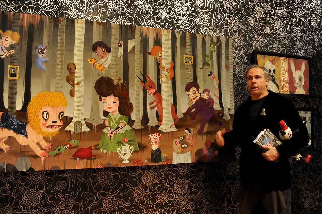 """. Gary Baseman stands by a painting in the study of his exhibition \""""Gary Baseman: The Door is Always Open,\"""" at the Skirball Cultural Center, Wednesday, April 24, 2013. Baseman\'s work is known for his vibrant, cartoon-like, artistic style in publications such as The New Yorker, Rolling Stone and the LA Times. He designed for the game Cranium and created the animated TV series, Teacher�s Pet.The exhibition design is based on his childhood home in LA�s Fairfax district and includes family furniture and snapshots and many items of interior décor designed by the artist, including wallpaper, pillows, a chandelier and more. (Michael Owen Baker/Staff Photographer)"""