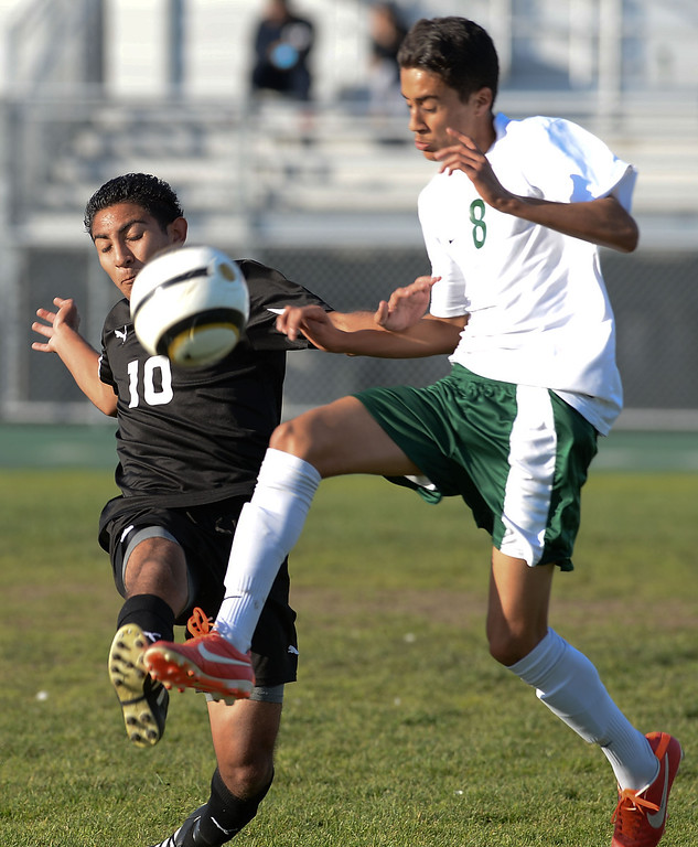 . Narbonne\'s Jaime Enriquez (8) pushes the ball through San Pedro\'s Andres Toribio (10) in a Marine League boys soccer game Wednesday, February 12, 2014, Harbor City, CA.  Narbonne won 2-0 and seals the league title. Photo by Steve McCrank/Daily Breeze