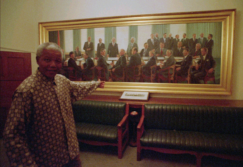 ". SOUTH AFRICA NEW PARLIAMENT  --South African President Nelson Mandela points to a painting of the apartheid-era all white cabinet of former Prime Minister P. W. Botha, which hangs in the main hall in the parliament building in Cape Town, South Africa in April, 1995. Mandela said that the painting must be removed because it doesen\'t represent the reality of the ""New South Africa.\"" AP PHOTO/Benny Gool)"