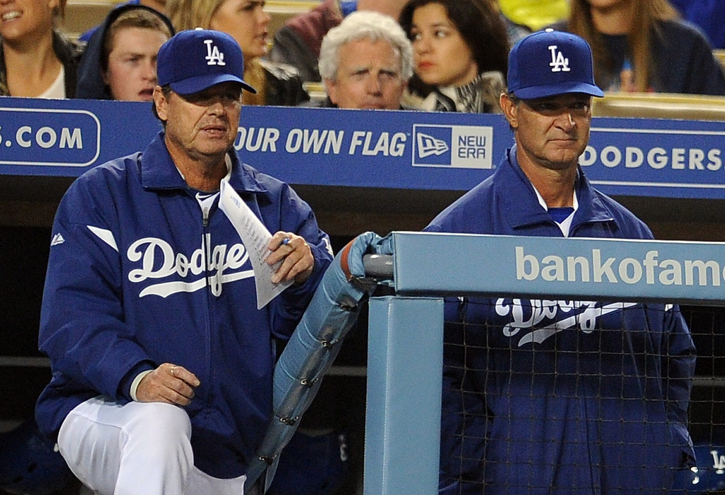 . Los Angeles Dodgers pitching coach Rick Honeycutt, left, along with manager Don Mattingly look toward the mound after San Francisco Giants\' Hunter Pence (not pictured) hit a solo homerun in the sixth inning of their baseball game on Wednesday, April 3, 2013 in Los Angeles. 