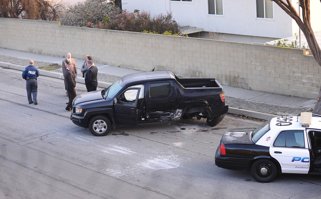 . Law enforcement investigators at the scene of a bullet-riddled black truck on Flagler Lane in Redondo Beach Thursday morning. It appeared that the police car at right and the truck collided and the truck also had several bullet holes in the windshield.Photo by Brad Graverson 2-7-13