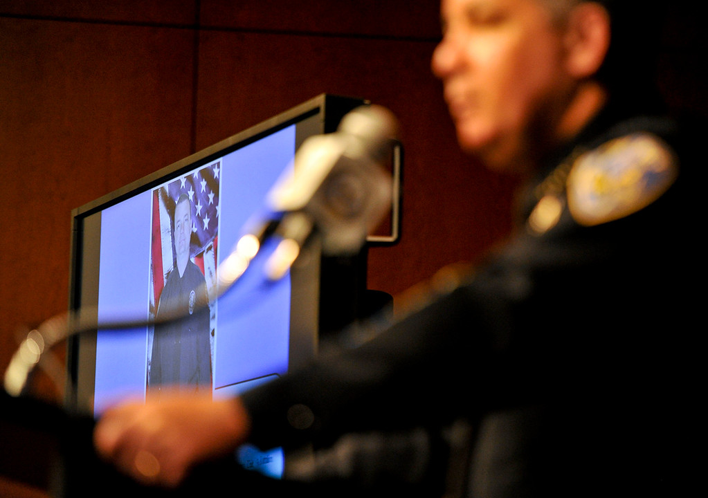 . A photograph of slain Riverside police officer Michael Crain is displayed on a screen as Riverside Police Chief Sergio Diaz gives the latest updates in the search for fugitive ex-LAPD officer Christopher Dorner at a press conference at the D.A.\'s office in Riverside on Monday, Feb. 11, 2013. (Rachel Luna / Staff Photographer)