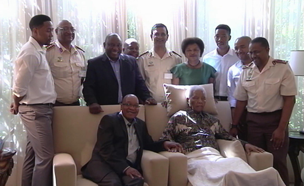 . In this image taken from video, South African President Jacob Zuma, centre left, sits with the ailing anti-apartheid icon Nelson Mandela, centre right, is filmed Monday April 29, 2013, with unidentified members of his family and his medical team as they pose together more than three weeks after Mandela was released from hospital. Mandela was treated in hospital for a recurring lung infection.  South African President Jacob Zuma visited the former leader on Monday, but Mandela does not appear to speak during the televised portion of the visit, as he sits in an armchair, his head propped up by a pillow and with his cheeks showing what appear to be marks from a recently removed oxygen mask, although Zuma said he found Nelson Mandela �in good shape and in good spirits�. (AP Photo/SABC TV)