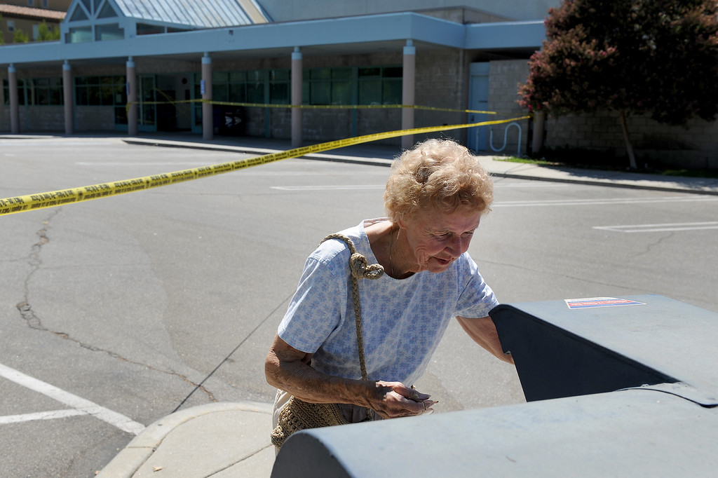 . A woman who didn\'t give her name places an envelope in the mailbox at the West Hills post office on Sherman Way after a car crashed into the lobby Thursday morning, August 22, 2013. One person inside the post office was hurt and the post office closed for the day. (Michael Owen Baker/L.A. Daily News)