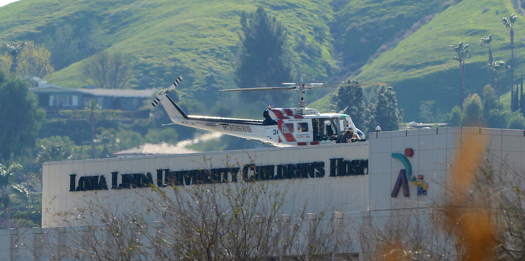 Description of . Injured deputies are unloaded off of a San Bernardino County Sheriff's helicopter at Loma Linda University Medical Center on Tuesday, February 12, 2013 after exchanging gunfire with suspect Christopher Dorner in the mountains of San Bernardino near Angeles Oaks, CA. Mandatory Credit/Courtesy Steven K Doi