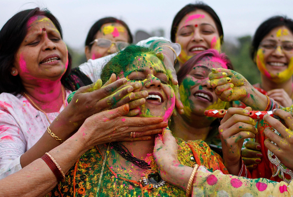 Description of . Indian women smear colors on each others faces as they celebrate