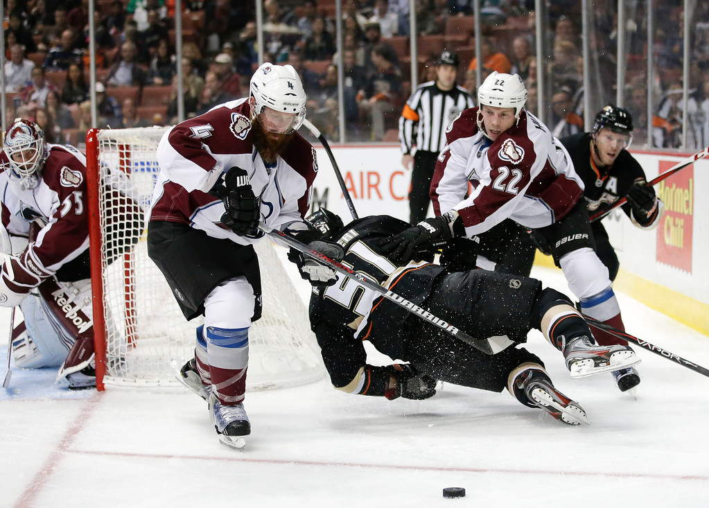 . Anaheim Ducks\' Kyle Palmieri, center, falls to the ice as he fights for the puck with Colorado Avalanche\'s Greg Zanon, left, and Matt Hunwick during the second period of an NHL hockey game in Anaheim, Calif., Wednesday, April 10, 2013. (AP Photo/Jae C. Hong)