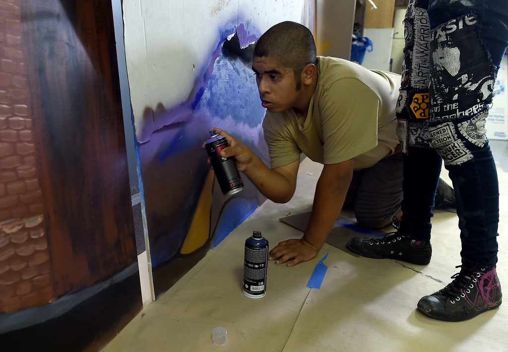 Description of . Christian Ornelas, 17, of Pomona, continues working on a mural at the San Gabriel Valley Conservation Corps YouthBuild Charter School in Pomona, CA, Wednesday, August 13, 2014. (Photo by Jennifer Cappuccio Maher/Inland Valley Daily Bulletin)