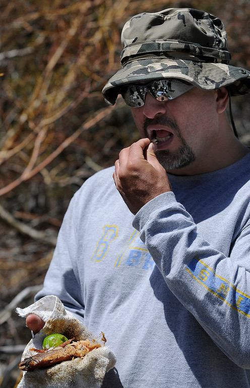 . George Torres eats some fresh cooked trout on the shoreline at Convict Lake on opening day of Trout Fishing Season in the Eastern Sierra. Convict Lake, CA 4/27/2013(John McCoy/Staff Photographer)