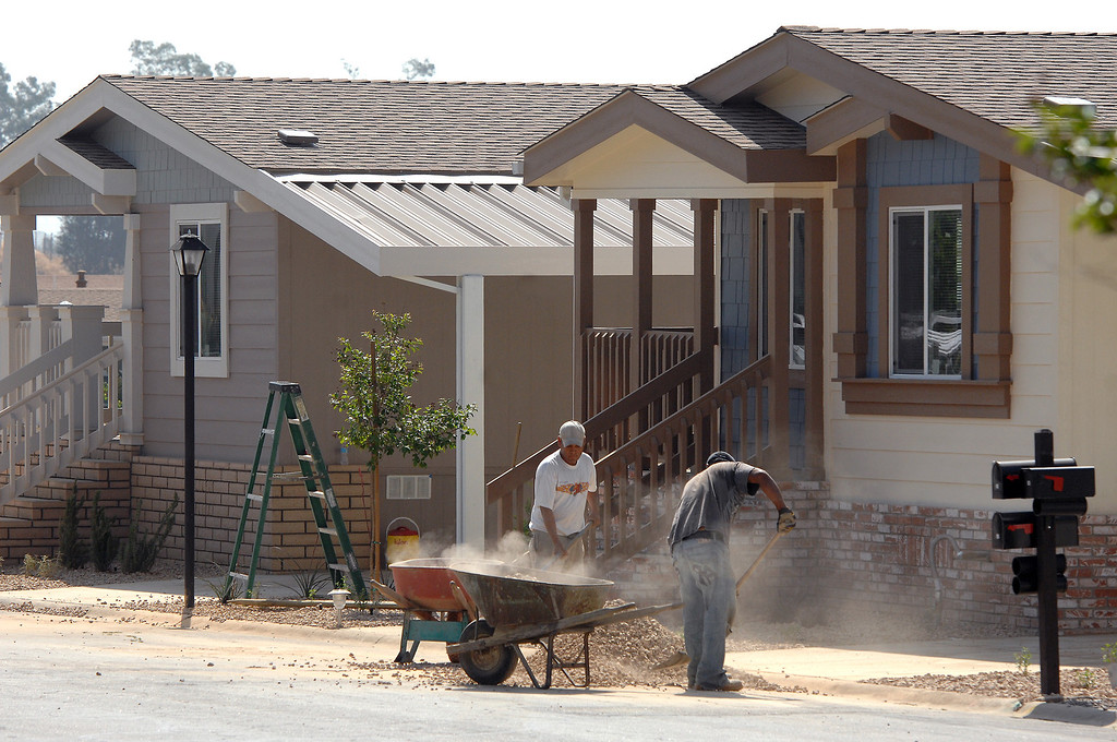 . Workers shovel gravel while working on the landscaping at Oakridge Mobile Home Park in Sylmar, Tuesday, April 23, 2013. (Michael Owen Baker/Staff Photographer)
