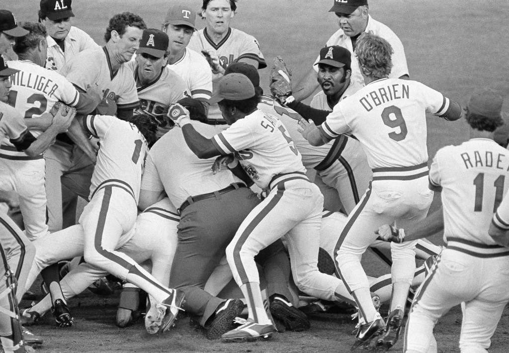 . Second base umpire Dale Ford is caught in the middle of a bench-clearing brawl between the California Angels, and the Texas Rangers in Arlington, Texas, June 23, 1983. Both benches emptied onto the field when Angels\' second baseman Bobby Grich blocked Rangers Wayne Tolleson\'s path back to second in the first inning, on a pick off attempt. (AP Photo/David Breslauer)