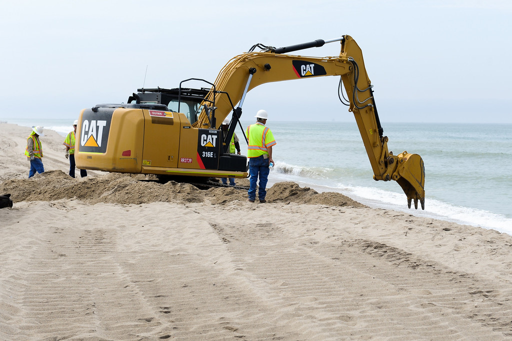 . A Ventura County Public Works crew digs a trench for the pump pipe in the sand berm which has closed off the mouth of the Santa Clara River estuary and flooded the campground at McGrath State Beach Park in Oxnard, Monday, July 22, 2013. (Michael Owen Baker/L.A. Daily News)