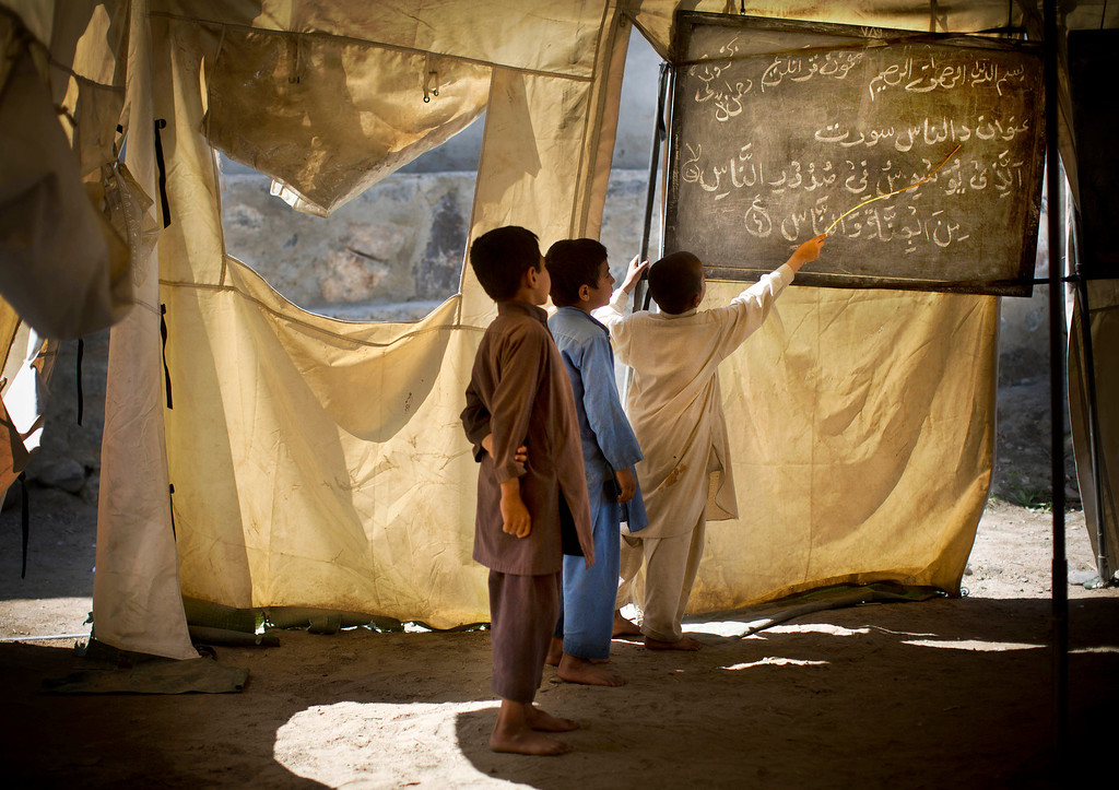 . Afghan boys study at a makeshift school in the village of Budyali, Nengarhar Province, Afghanistan, Tuesday, March 19, 2013. Providing education to Afghan boys and girls was a priority after the collapse of the Taliban, who refused to educate girls. (AP Photo/Anja Niedringhaus)