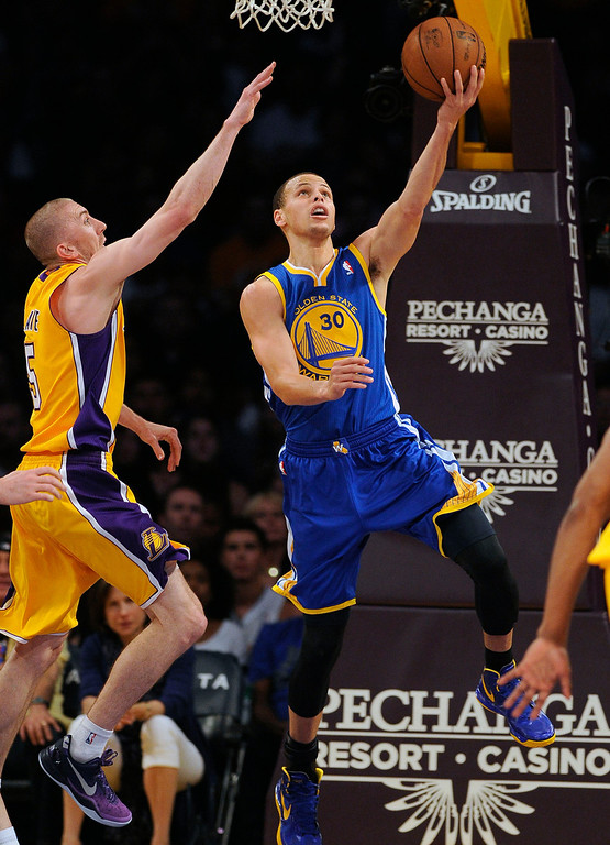 . The Warriors\'  Stephen Curry #30 lays the ball up as the Lakers\' Steve Blake #5 defends during their game at the Staples Center in Los Angeles Friday, April 12, 2013. (Hans Gutknecht/Staff Photographer)
