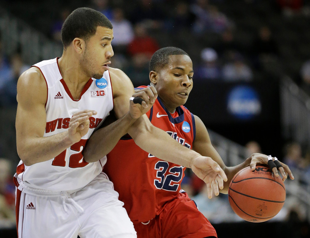 . Mississippi guard Jarvis Summers (32) is fouled by Wisconsin guard Traevon Jackson (12) during the first half of a second-round game in the NCAA college basketball tournament at the Sprint Center in Kansas City, Mo., Friday, March 22, 2013. (AP Photo/Orlin Wagner)