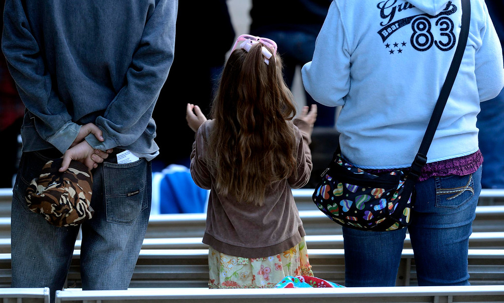 Description of . A little girl raises her hands in worship during Easter Sunrise services at the Roosevelt Bowl in San Bernardino March 31, 2013.  GABRIEL LUIS ACOSTA/STAFF PHOTOGRAPHER.