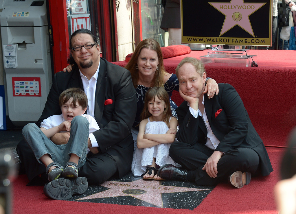 . American illusionists and entertainers Penn Jillette (L, with his wife and children) and Teller are honored with a star on the Hollywood Walk of Fame on April 05, 2013 in Hollywood, California. AFP PHOTO/JOE KLAMAR        (Photo credit should read JOE KLAMAR/AFP/Getty Images)