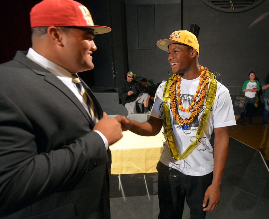 """. Long Beach Poly football player John \""""JuJu\"""" Smith, right, greets his friend and fellow USC signee Damien Mama from St. John Bosco following his announcemtn that he will play football for USC during a ceremony at Poly in Long Beach, CA on Wednesday, February 5, 2014. (Photo by Scott Varley, Daily Breeze)"""