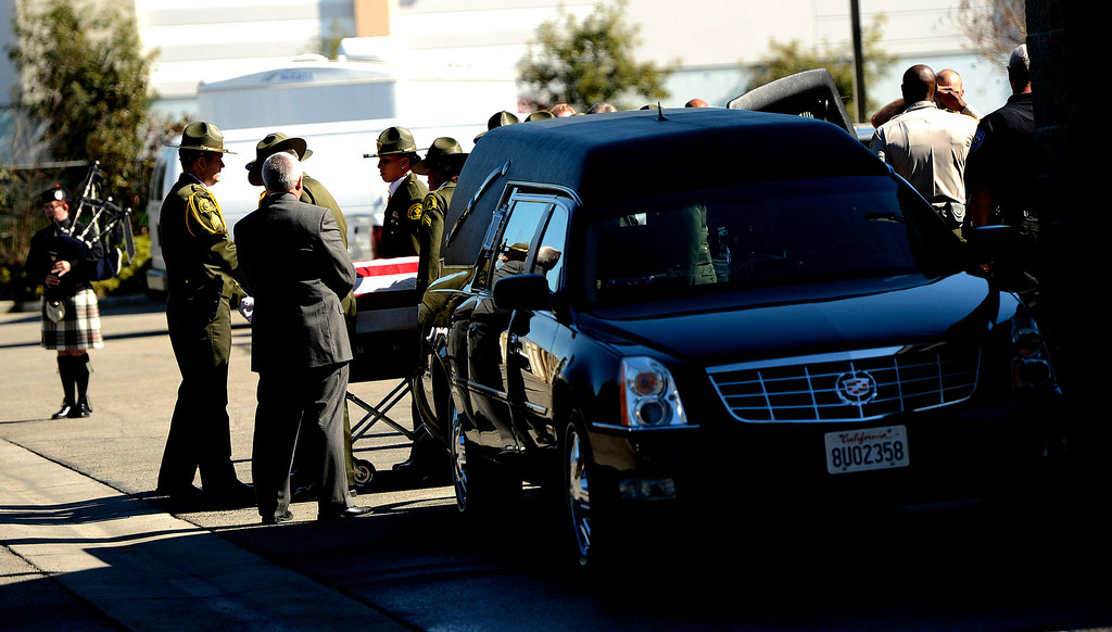 . The body of San Bernardino County Sheriff\'s  Deputy Jeremiah MacKay is loaded into a hearse at the SBCO Coroner\'s Office in San Bernardino February 14, 2013. The Department held a small service with Honor Guard, and the playing of bag pipes prior to a procession led by a motorcade to Mountain View Mortuary in San Bernardino.  McKay was the final victim of fugitive Christopher Dorner.   GABRIEL LUIS ACOSTA/STAFF PHOTOGRAPHER.