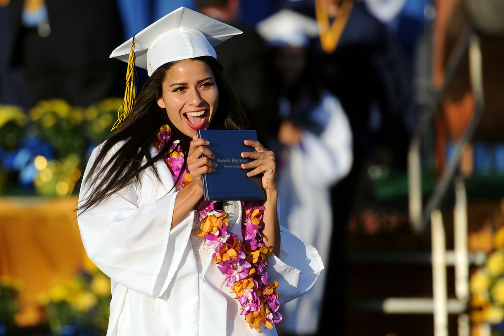Description of . Christine Bravo reacts after receiving her diploma during the Montebello High School commencement at Montebello High School on Thursday, June 20, 2013 in Montebello, Calif.  (Keith Birmingham/Pasadena Star-News)